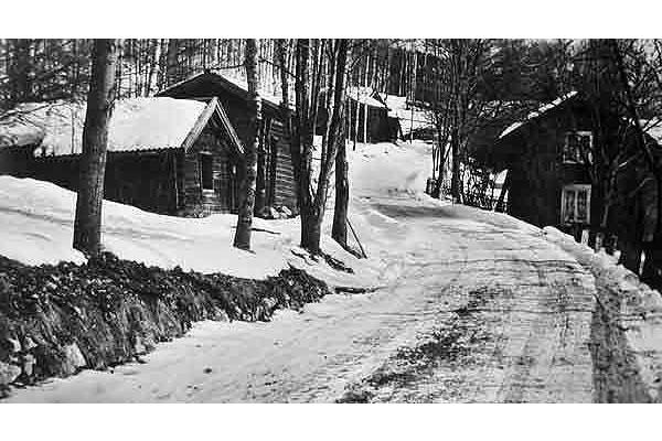 Modigsbacken T h intill landsvägen syns den gamla Erkersgården, som fanns före storskiftet. Byggnaden flyttades 1944/45 längre in på gårdsplanen till nuvarande plats. Samtidigt gjordes en modernisering. Övriga byggnader som syns i backen är bortflyttade.